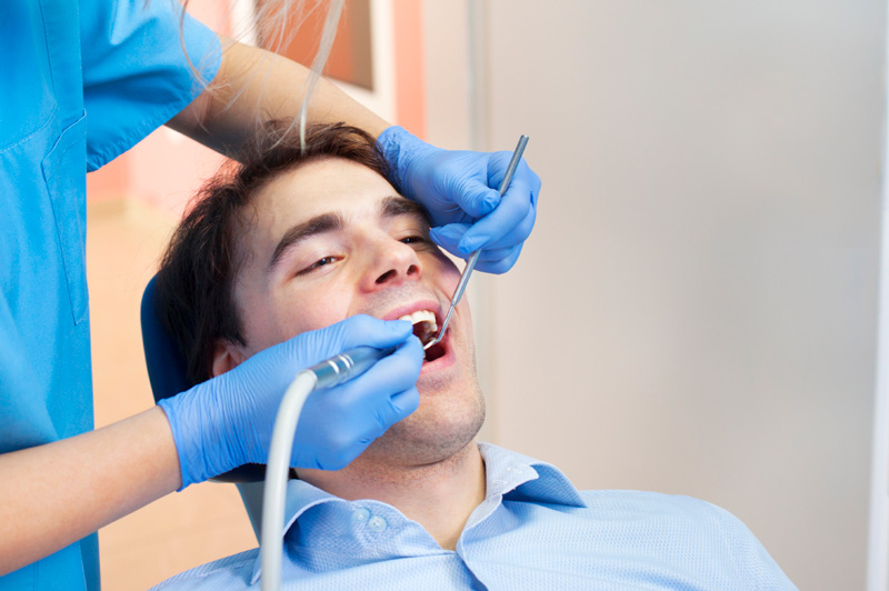 Man receiving dental cleaning at Reich Dental Center – Roswell in Roswell, GA.